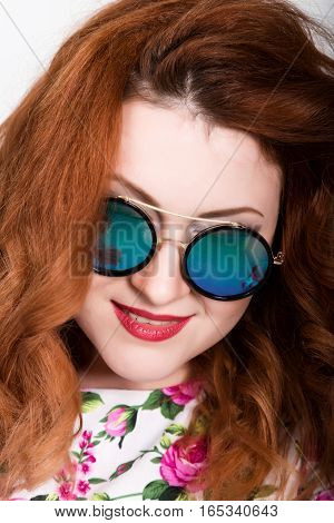 young stylish red-haired woman with curly hair and pretty face posing in sunglasses. expresses different emotions.