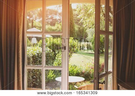 Open door and nature. Green plants and sunlight. House with a garden.