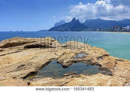 Rio de Janeiro Ipanema beach Gavea stone and Two Brothers hill seen through the Arpoador stones