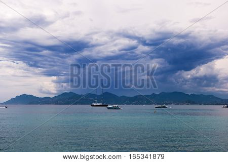 Sea and yachts. Gloomy sky over mountains. The storm is coming.