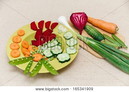 Fresh beet,carrot,green onion,peas on the plate,tablecloth and board.Vitamin vegetable.Healthy organic food.