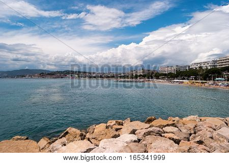 Buildings on sea coast. Water and blue cloudy sky. Spend unforgettable summer at resort.