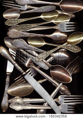 Many antique spoons knives forks isolated on black background. Old silver cutlery decorated with floral pattern for serving food. Vintage fancy tableware