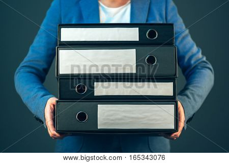 Accountant holding document binders with archived paperwork and other corporate legal sheets mock up copy space