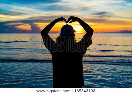 Sillouete Woman being love sign hand symbol in sunset.