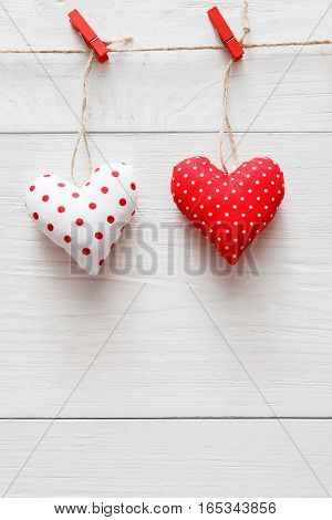 Valentine background with sewed pillow diy handmade hearts couple on red clothespins at rustic white wood planks. Happy lovers day card mockup, copy space, vertical