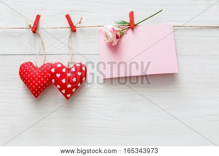 Valentine background with sewed pillow diy handmade hearts and empty greeting card on red clothespins at rustic white wood planks. Happy lovers day mockup