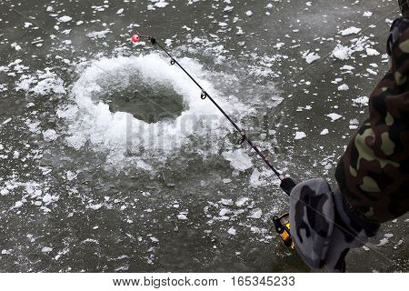 A hole in ice and fishing rod in the hand of fisherman