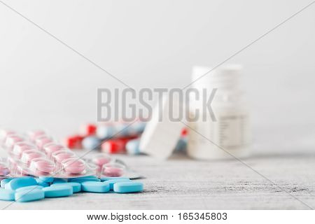 Colorful medication and pills on white table