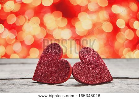 Valentine background with handmade glitter hearts on rustic wood with holiday lights bokeh background. Happy lovers day party invitation card mockup, copy space
