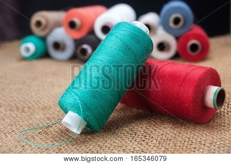 Colored spools of thread on the sackcloth