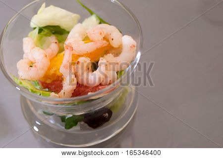 Salad with shrimps on the glass plate