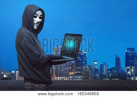 Hooded Hacker With Anonymous Mask Typing On Laptop