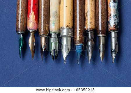 Fountain pen collection. Calligraphic accessories, aged colorful artist pens, textured blue paper background. Artist workshop concept. macro, up view, soft focus.
