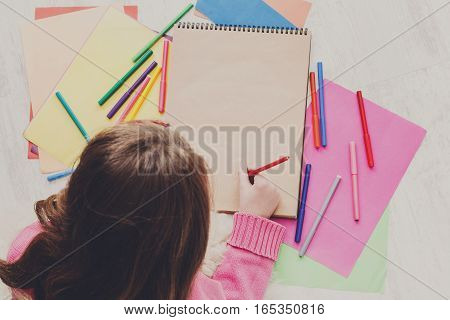 Girl drawing picture with colored markers, crayons and pencils. Top view from above, copy space on paper sheet. Creative children, child art school or courses concept