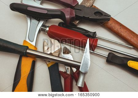 tools. Screwdriver hammer and pliers over white
