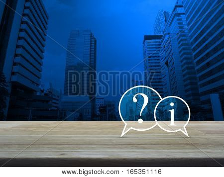 Question mark and information chat icon on wooden table over modern office city tower background Customer support concept