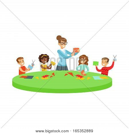 Four Children In Art Class Doing Applique Cartoon Illustration With Elementary School Kids And Their Teacher In Creativity Lesson. Happy Schoolkids Doing Paper Craft With Demonstration From Adult Woman.