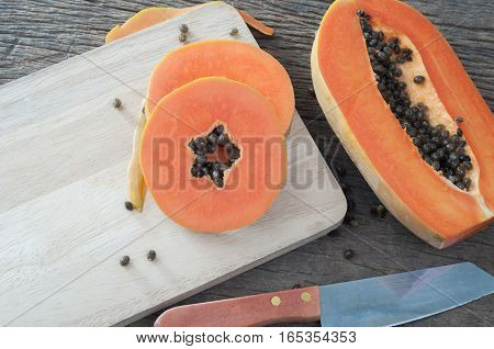 kitchen table with slice fresh papaya on wood cutting board Fruit for the digestive system selective focus on top view.