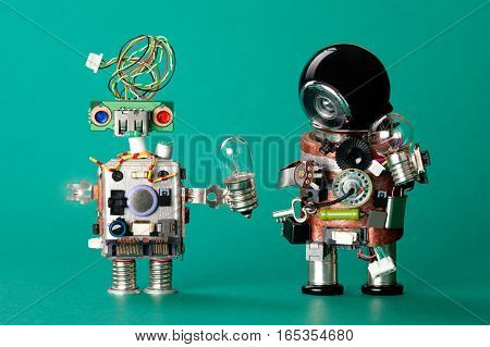 Toy robots with lamp bulbs. Circuits chip handyman characters, funny black helmet head, electric wire hairstyle colored blue red eyes. Modern steampunk heroes green background, soft focus.