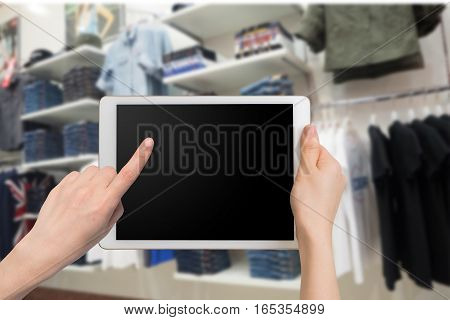 human hand hold and touch smartphone tablet cell phone with blurry Clothing racks. concept of shopping and finding clothes on application online.