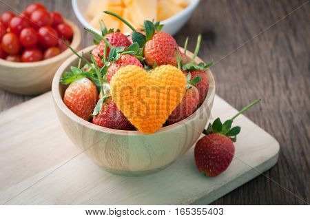 group of fresh ripe strawberry on wood plate with orange heart shape red tasty fruit on kitchen table. healthy eating and dieting food concept of health care Image focus top view.
