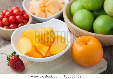 kitchen table with slice fresh persimmon on cutting board Asian tropical fruit Image focus top view. healthy eating and dieting food concept of health care Image focus top view.