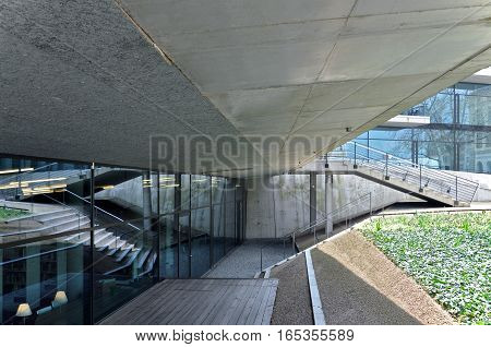 Dresden, Germany - April 12, 2016: Architectural composition. Fragment of a modern building with concrete canopy stairs and reflection in the glass.
