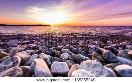 Stones On A Beach With Sunset On The Ocean Sea.