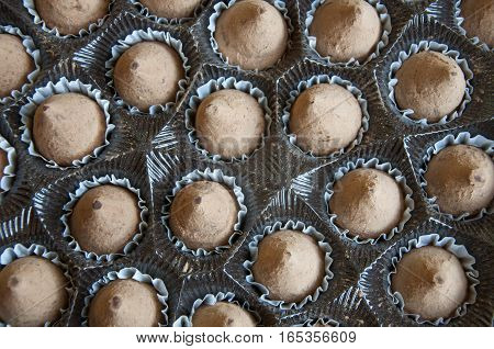 Lots of chocolate truffles in the open packaging box. Close-up.