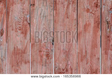 Fence of shabby weathered red-painted wooden planks for background in rustic style