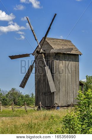 Old wind mill at the park with blue sky clouds.