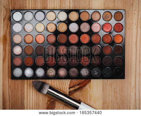 Female cosmetics. Brush with eyeshadows in wooden background