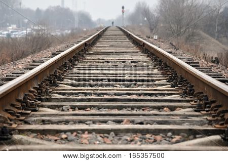 Old railroad tracks with wooden sleepers in perspective.