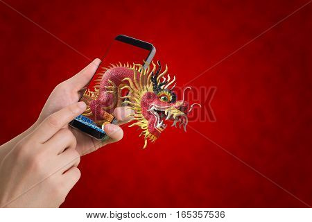 human hand hold smartphone tablet cell phone with big dragon statue come out screen. concept of celebrate Chinese New Year red background concept of the Year of the Dragon.