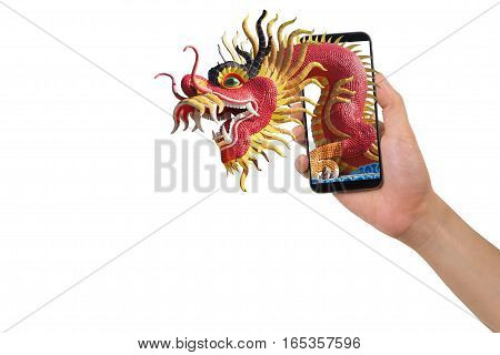human hand hold smartphone tablet cell phone with big dragon statue come out screen. concept of celebrate Chinese New Year background with concept of the Year of the Dragon.