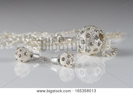 Closeup jewelry set of studded silver earrings and pendant on acrylic surface on grey background.