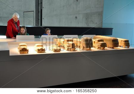 Stuttgart, Germany - April 22, 2014: Interior of modern museum of Mercedes cars. Exposition of wooden automobile models and visitors.