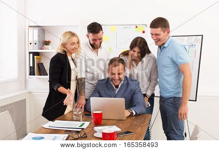 Happy business people laugh near laptop in the office. Successful corporate team of female and male coworkers joke and have fun together at work. Internet development concept