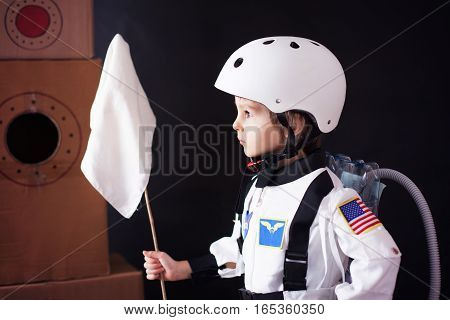 Beautiful Preschool Boy, Dressed As Astronaut, With Flag And Carton Rocket