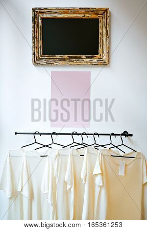 Six identical thin white t-shirts from organic cotton on black hangers beneath an empty black sign in a vintage frame on white wall