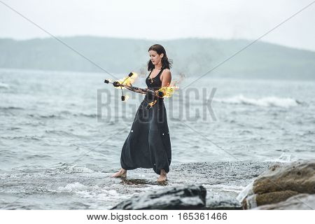 on the shore of the sea girl is playing with fire