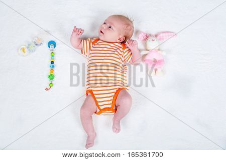 Cute adorable newborn baby girl one month old. New born child, little girl with toy and pacifier dummy as nomber one. Family, new life, childhood, beginning concept.