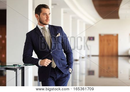 handsome young businessman in a stylish modern office space with large windows