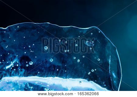 Ice texture closeup. Frozen water and air bubbles. Transparent abstract shape object cold blue winter background. Soft focus photo