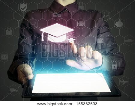 Image of a girl with a tablet in hands. She presses on the icon graduation hat cap. Online education concept choose of career