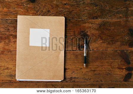 Craft brown office folder with empty white label and a ballpoint black pen on a rustic dark brown table, top view