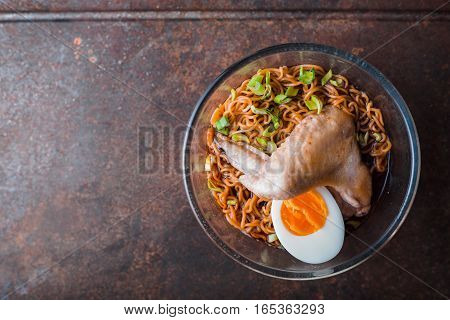 Soup Ramen noodle with chicken wing on the old table vertical