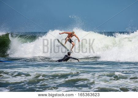 BELMAR NEW JERSEY-AUGUST 1- A young man rides a wave in rough surf on August 1 2015 in Belmar New Jersey.