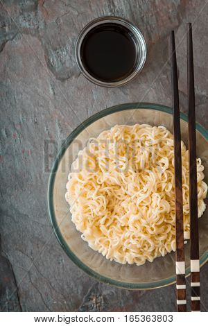 Soup Ramen noodles in glass bowl and sause on tte gray table vertical